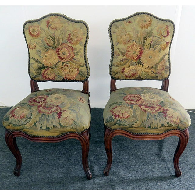 Pair of Louis XVI style side chairs with needle point upholstery and nail head trim.