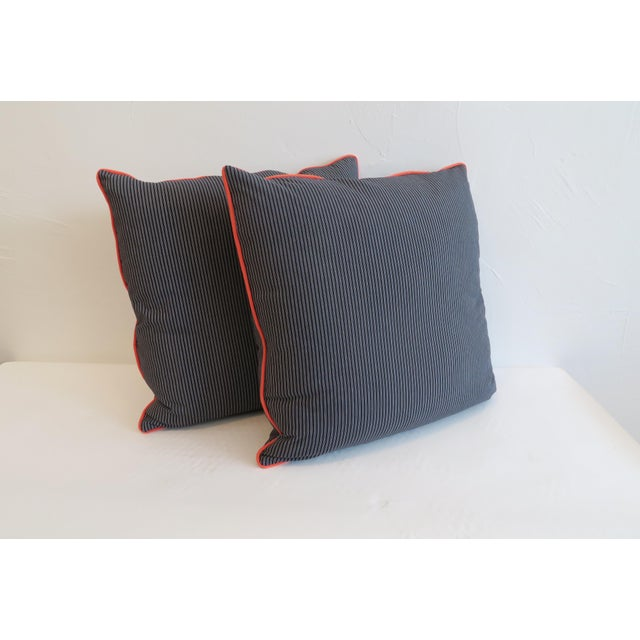 Pair of Custom pillows in cotton navy stripe with orange welt trim. Zipper closure and synthetic down fill.