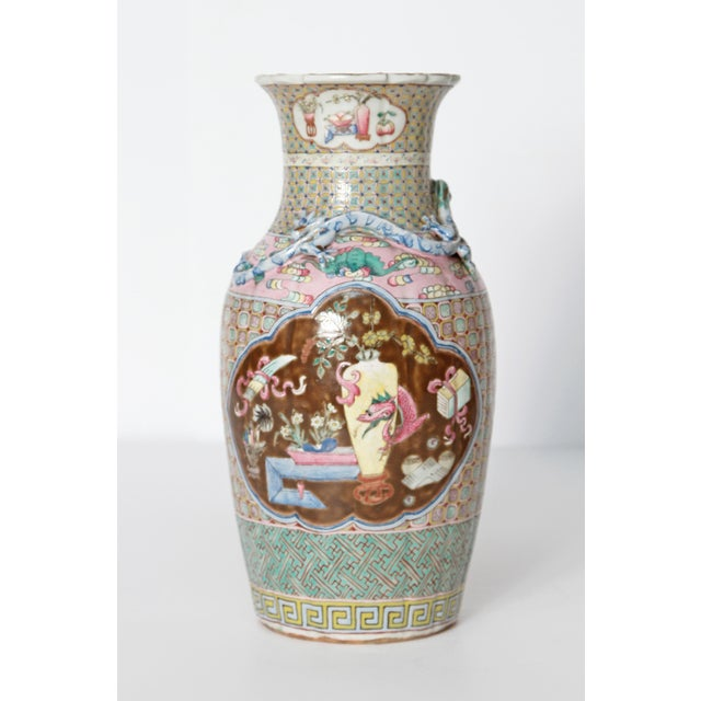 A pair of Chinese vases with all over variety of patterns on pink and turquoise with cartouches of brown background with...