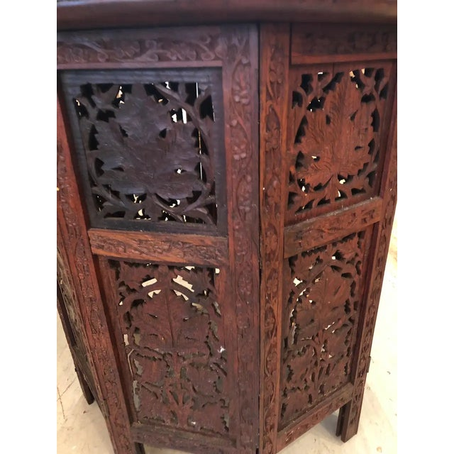 Intricately carved Moorish round end table with leafy foliage decoration and lovely inlay. Base is octagonal carved wood...