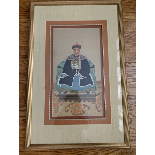 This pair of Chinese ancestral funeral portraits features a Patriarch and Matriarch and are enclosed in gold frames with...