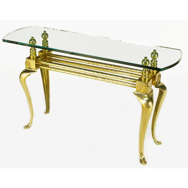 Cast and polished brass cabriole leg glass top console table. Twisted brass tube double stretcher connects brass cubes and...