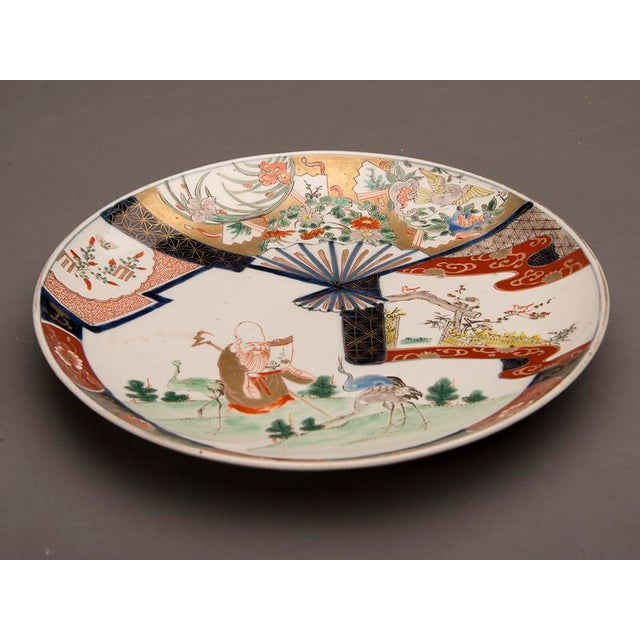 Asian An Imari charger from Arita, Japan c. 1875 featuring a scholar reading a scroll in a landscape surrounded by three cranes For Sale - Image 3 of 7