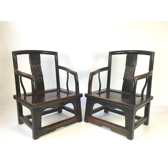 Antique Asian pair of 2 elegantly made rosewood Chinese official's chairs, circa 1930s. The center yoke back panel has a...
