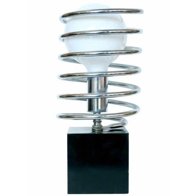 This Modernist spring table lamp features a black steel cube with a chrome socket surrounded by a large chrome coil...