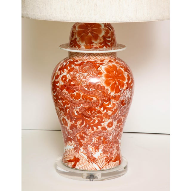 A pair of orange and white Chinese ceramic jars, converted to lamps, with linen shades and a Lucite base. A great (and...
