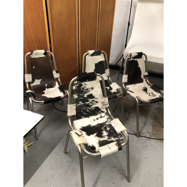 Cowhide sling chairs on tubular metal frame. Comfortable. Stackable chairs. (See Charlotte Perriand chairs). Price shown...