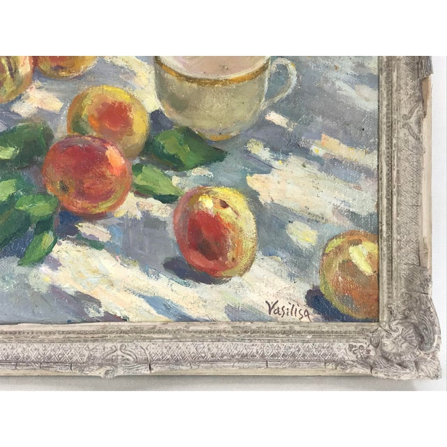 Vintage oil painting of peaches and teacup on an outdoor table in dappled light. The summery scene is impressionistic in...