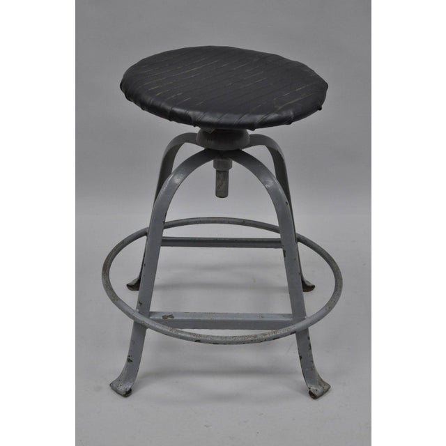 Antique American Industrial Grey Steel Metal Adjustable Work Stool with Black Vinyl Seat. Age: Early to Mid 20th Century,...