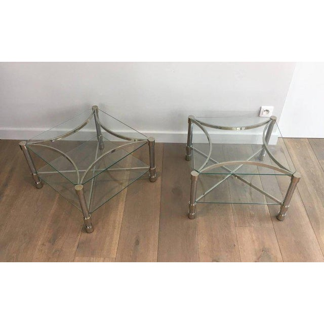 An unusual pair of square chromed brass side tables with rounded legs. The bottom glass shelf is supported on an...