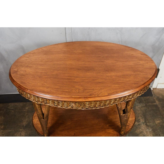 This 1930's wicker table has a solid wood oval top with a veneered lower shelf. The table has the original finish with...