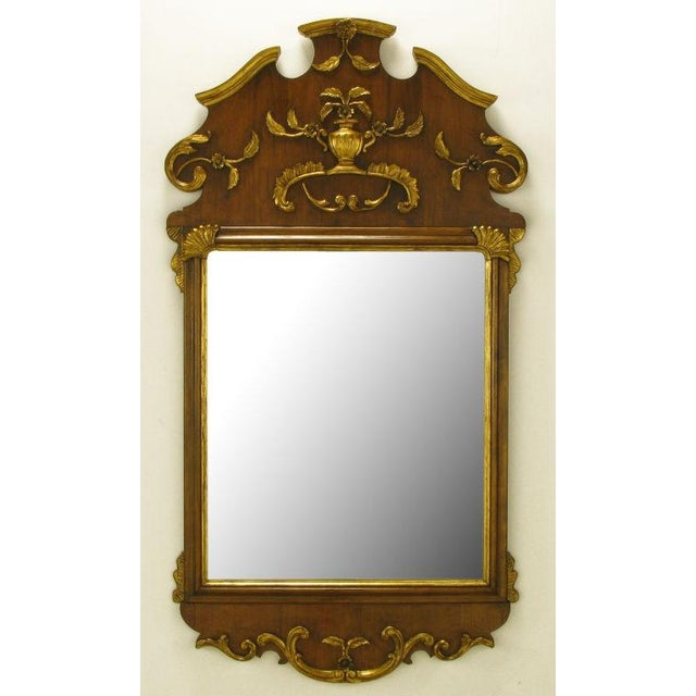 Walnut wood with carved and gilt Italianate detail style mirror. Top detailing features a floral accented urn and rococo...