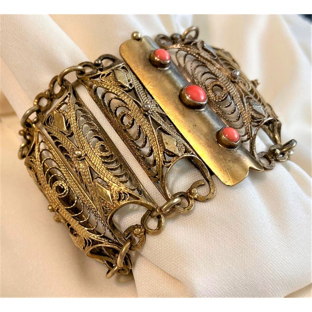 """Circa 1940 plated brass filigree link bracelet with a slide clasp bezel set with three coral cabochons. It measures 7.12""""..."""