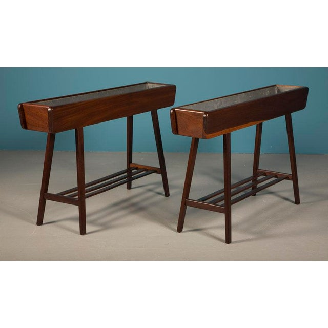 A pair of jardinière stands comprising a walnut cased top in a rectangular box with galvanized steel liners supported by...