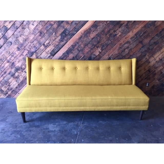 Mid-Century style custom sofa made in Los Angeles. Can be made with choice of color and fabric. This one has a tufted back...