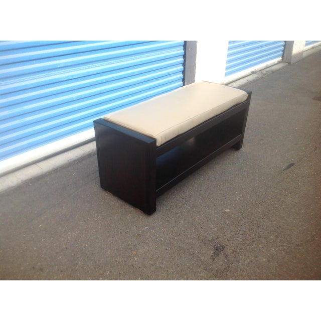 Modern ottoman with cream color leather cushion. The ottoman is made of alder with rich walnut finish. The ottoman is n...