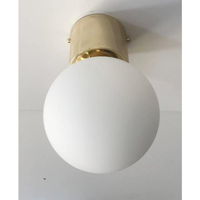 Italian modern flush mount with matte white Murano glass globe and chic polished brass finish / Designed by Fabio Bergomi...