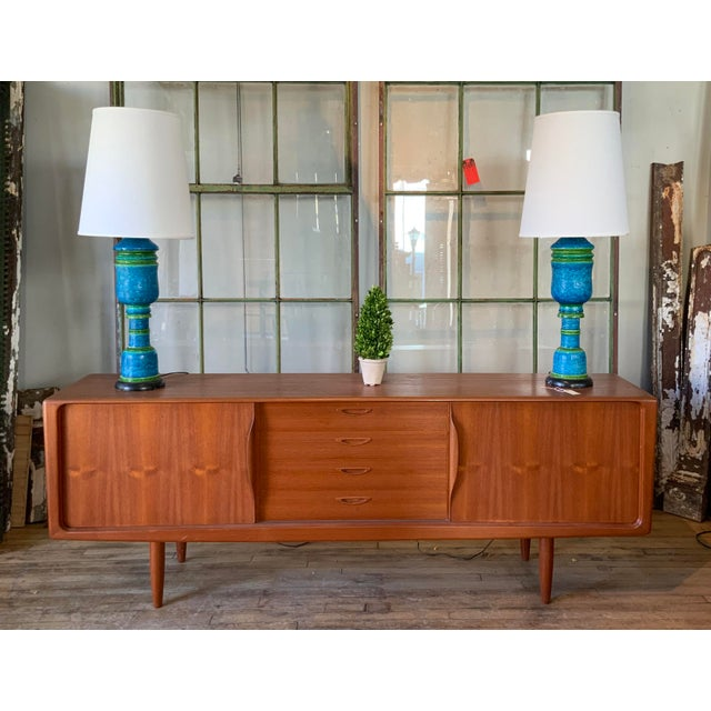 A beautiful and handsome 1950s Danish teak credenza cabinet, with sliding doors with integrated sculptural handles, which...