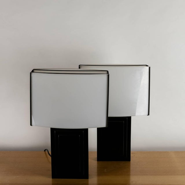 Set of two Italian 1970s table lamps featuring lacquered base and curved plexiglass diffusers.