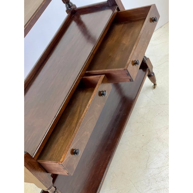 Early 20th Century three-tiered English serving trolley or console server of mahogany made in the Regency style. The...