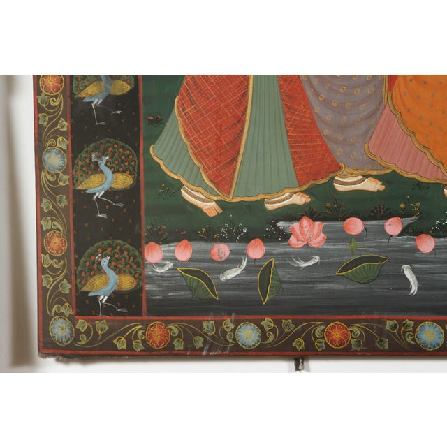 A large Pichhavai painting of Krishna with female Gopis dancing Krishna playing flute on a bed of lotus, the composition...