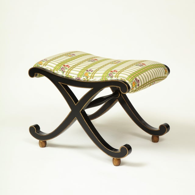 The upholstered rectangular seat covered in a trellis cotton print over a gilt-edged black X-form base resting on gilt...