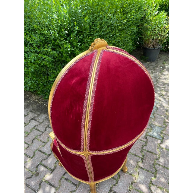 A wonderful French Balloon Arm chair in children size. The chair was reupholstered in dark red tufted velvet and the solid...