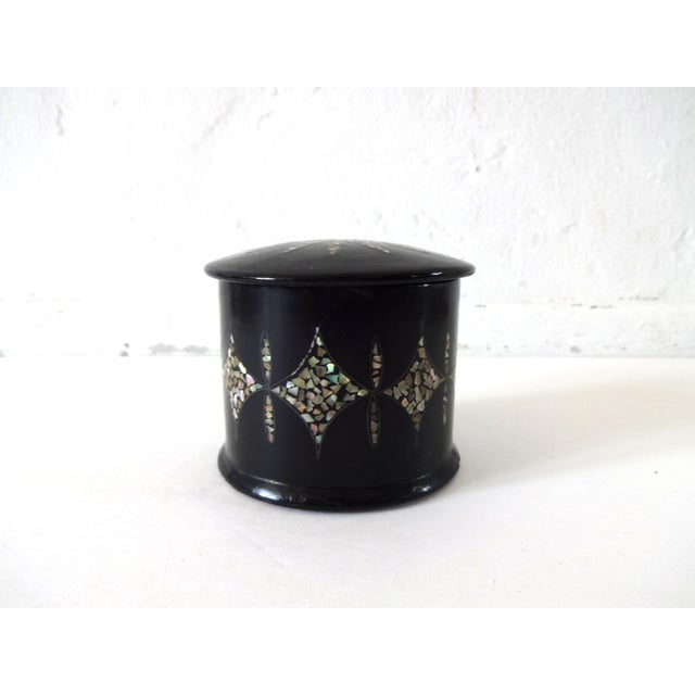 An antique piece of French Napoleon III papier mache. A round powder or trinket box, inlaid with mother of pearl in a star...
