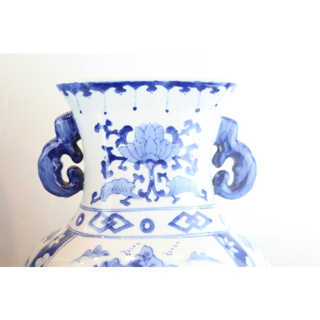 Blue and white porcelain village patterned Chinese urn with double handles.