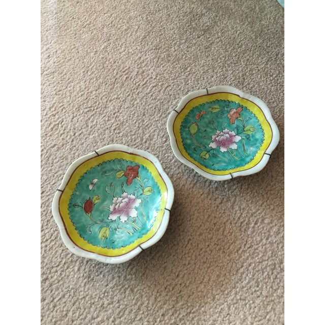 A delightful pair of 1930's colorful hand painted ceramic wall plates with wire hangers. Scalloped playful hand made rim.