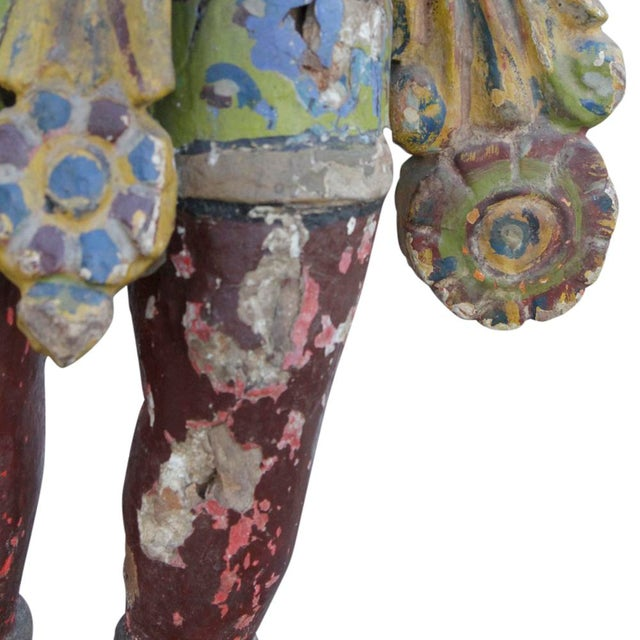 This antique polychrome statue depicts a fierce tribal warrior, and still retains its original color. Some damage.