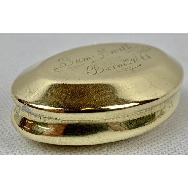 """A simple oval brass snuff box engraved """"Sam Smith, Birmingham 1861"""". This is a snuff box that would have been found in the..."""
