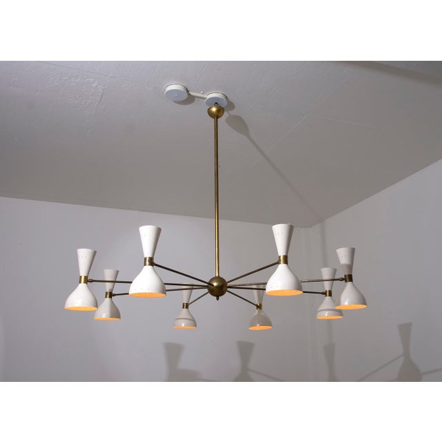 A stunning eight arm chandelier by Stilnovo. Lamps are diabolo shaped shades in enameled metal with both up and down...