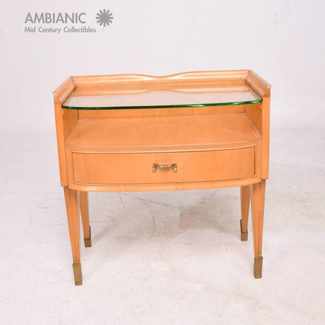 For your consideration a vintage Italian modern nightstand in blond wood with glass top and brass sabots. Elegant...