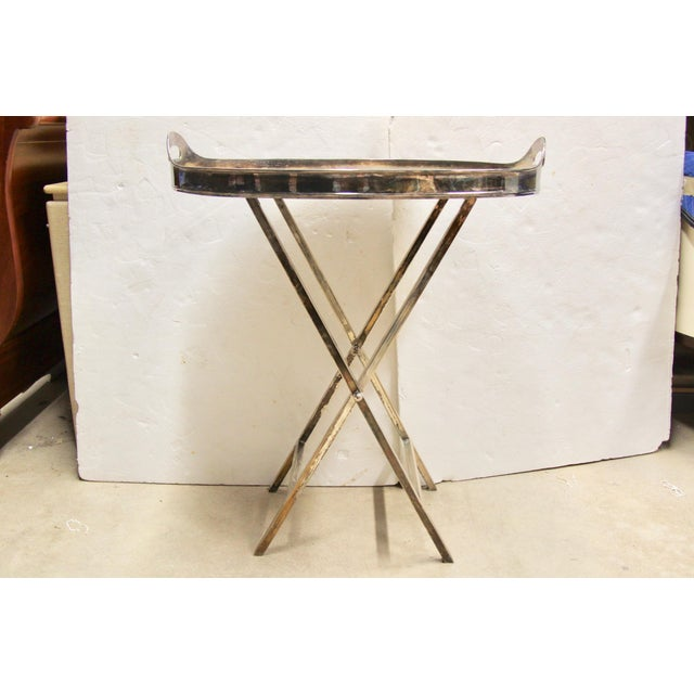 Handsome silver-plated folding tray table. Features an oval handled tray that sits atop a silver-plated base with faux...