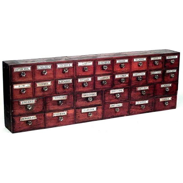 Pair of English Victorian Country style mahogany apothecary cabinets with four rows of drawers and clear glass knobs.