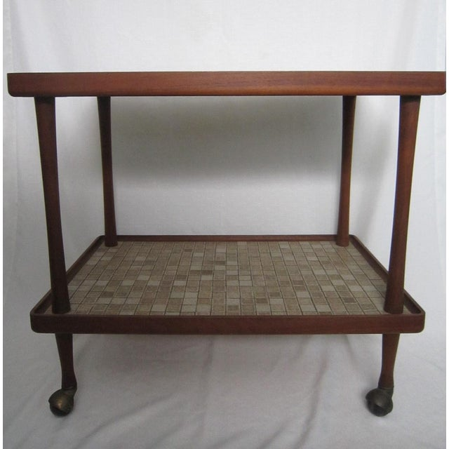Large two tier teak tea cart with tiled shelves. On rollers for easy movement. The tiles are a greige/beige color.