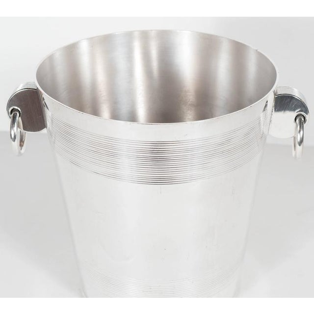 A handsome English Art Deco silver-plate ice bucket with stylized ring handles. A striped relief band is featured on the...