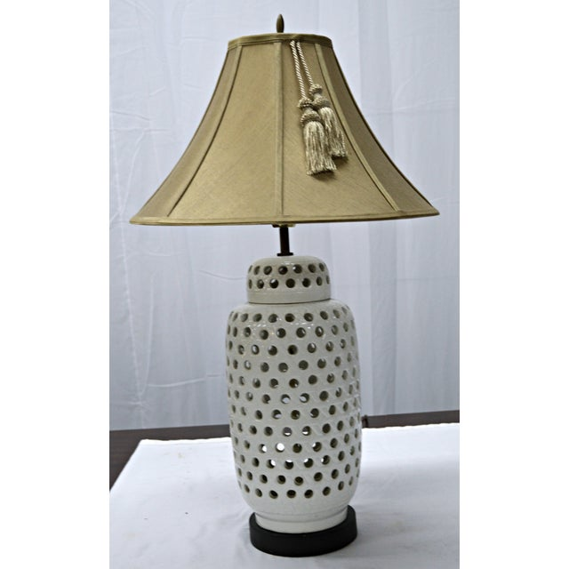 Mid-century perforated porcelain table lamp in a ginger jar shape. The lamp is on a round wood base. A silk shade with...