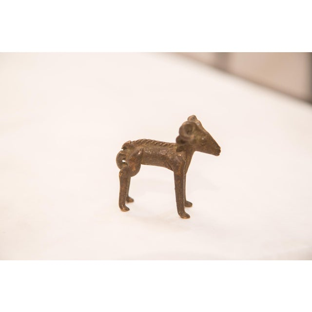 :: Vintage handmade bronze African sculpture of a ram, with shiny, iron-like patina. Circa mid 20th century and possibly...