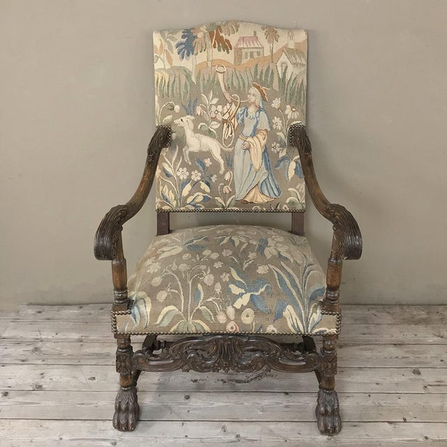 Antique French Louis XIII Armchair with Tapestry features a stately, masculine presence, with subtly arched seatback,...