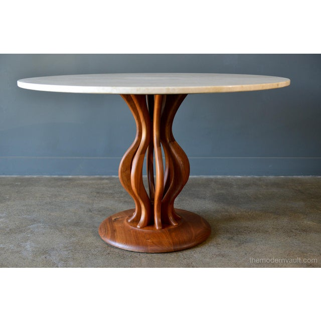 Travertine and sculpted walnut dining or bistro table by Brown Saltman, circa 1970. Beautiful sculpted walnut pedestal...