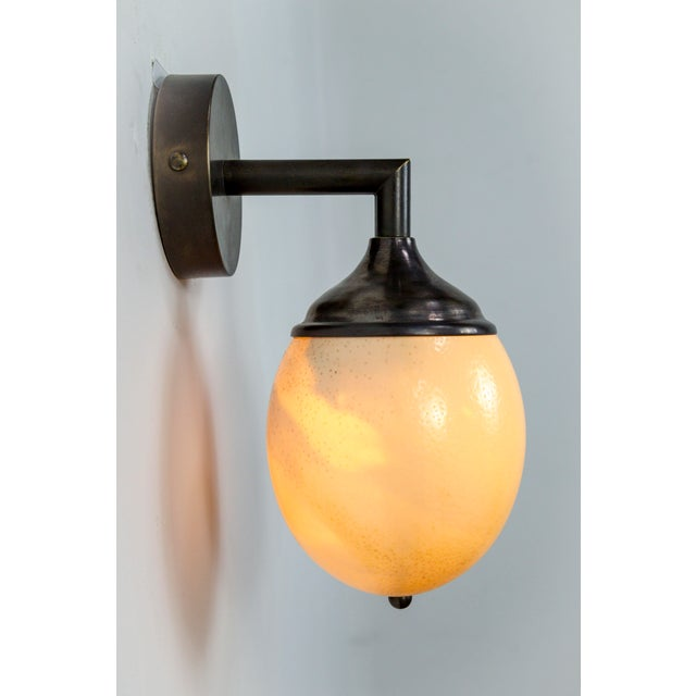 We used this pristine Ostrich egg with a beautiful texture, to compose this wall lamp with a cast brass arm, backplate,...