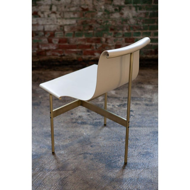 A Mid-century designed chair with Doral Cream color upholstery in light antique bronze finish, 1952. Designed by William...