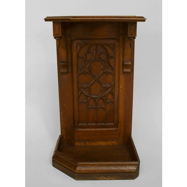 Turn of the century English Gothic style corner oak cane or umbrella stand with a tracery carved panel.