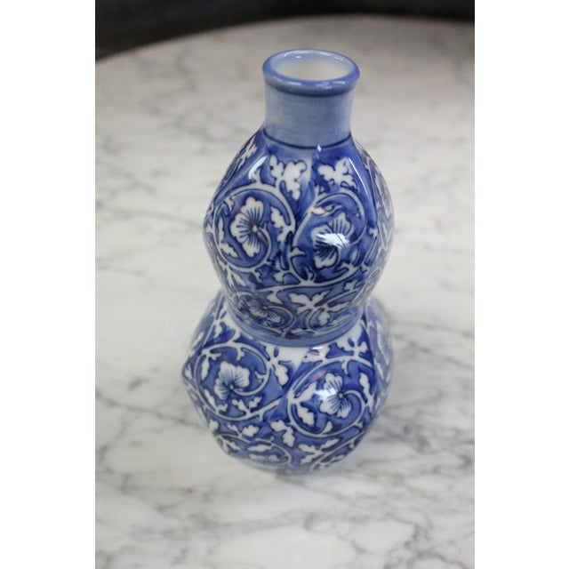 Unique Chinese cobalt blue and white floral patterned bud vase in swirled geometric form.