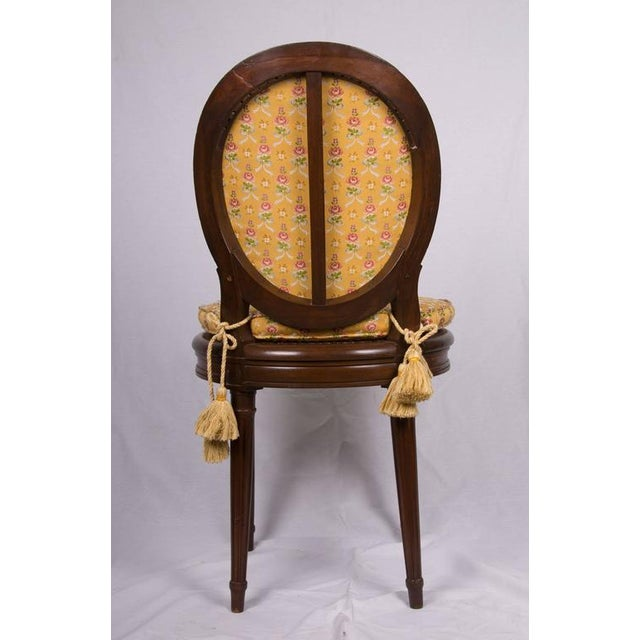 This is a pair of Louis XVI style walnut musician's chairs with upholstered open backs and caned seats with loose cushions...