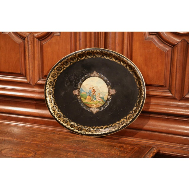 Elegant antique tray from France, circa 1870; oval in shape, the black tole platter is embellished by hand-painted gilt...
