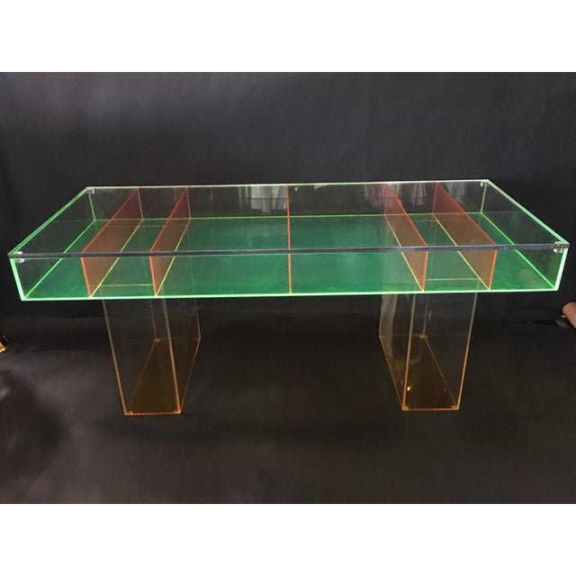 Custom multicolored Lucite coffee table. The tabletop base is lime green with bright orange legs and dividing pieces. The...
