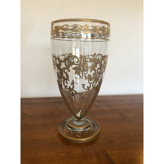 A beautiful medium sized vintage glass vase having ornate gold leaf patterned embellishments.